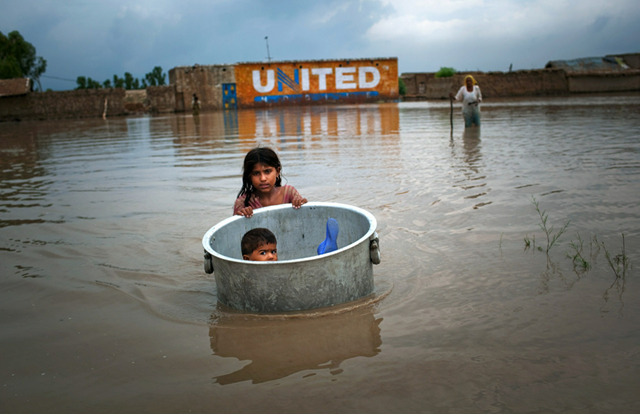 A girl floats her brother across flood waters while salvaging valuables from their flood ravaged home on 7 August 2010 in the village of Bux Seelro near Sukkur, Pakistan. Daniel Berehulak / Getty Images
