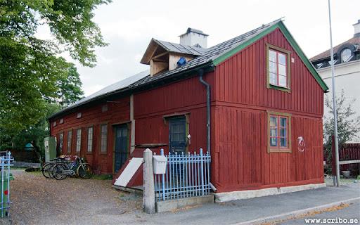Rött timrat uthus som innehöll svinstia, vedbod, tvätt och toa