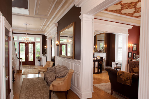 Front Foyer Featuring 12 foot ceilings, striking architectural details, original maple floors. Library and Parlor can be seen to the right. photo by Lee Brauer