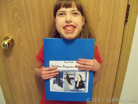 Supergirl holds her completed lapbook