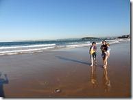 Nașă, fină și copii mergând pe plajă la reflux