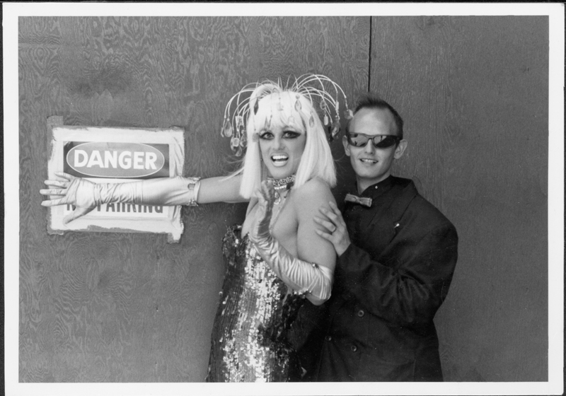 John Canally poses with a drag queen and danger sign. Undated.