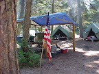 A typical campsite. Each has canvas tents on wooden platforms, dining shelters with picnic tables, washstand with running water, outhouse, and fire rings.