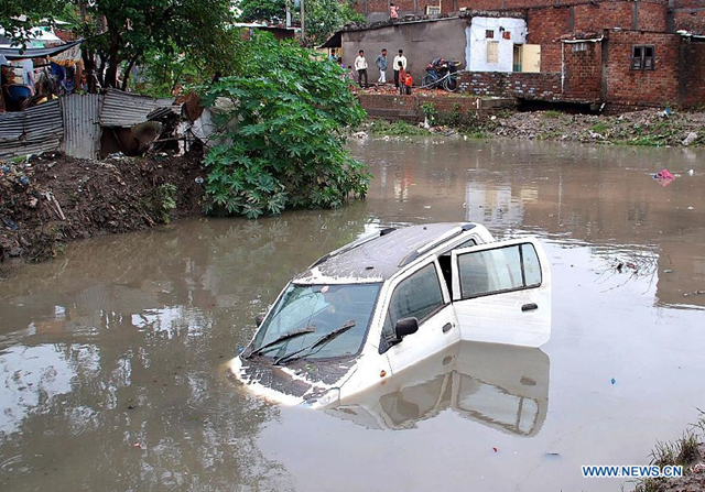 A car is submerged in water in the low-lying area after the heavy rains in Indore, Madhya Pradesh state, India, 4 July 2013. Heavy rains in the city caused flood in the low-lying area, disrupting traffic and normal life. Photo: Xinhua / Stringer