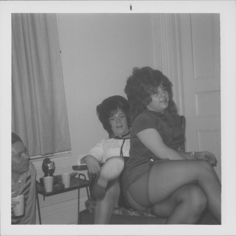Two drag queens share a chair at a party. Circa 1971-1974