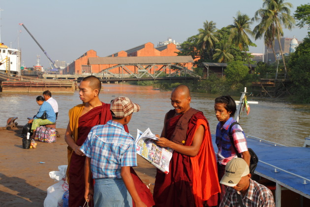 Buddhist Monk reads a newspaper at Yangon's ferry terminal