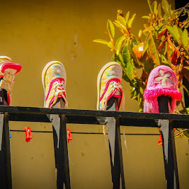 by Judith Dueck - Artistic Objects Clothing & Accessories ( graphic, decorative, colorful, foot, footwear, clothesline, children, yellow, slippers, child, girl, village, family, wash, pink, elements, light, shoes, dry, decoration, drying, beautiful, fence, pattern, background, summer, runners, small, design )