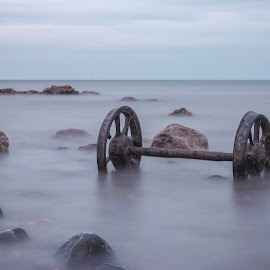 Rusty Wheels by Barrington Dent - Landscapes Waterscapes ( wheels, sea, rust )