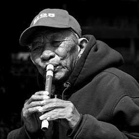 Man with flute by Gaylord Mink - Black & White Portraits & People ( flute, man playing flute, man with flute, man,  )