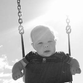 Confused by Missy McKane - Babies & Children Babies ( park, black and white, confuse, baby, grandson, swing, baby boy, sun )