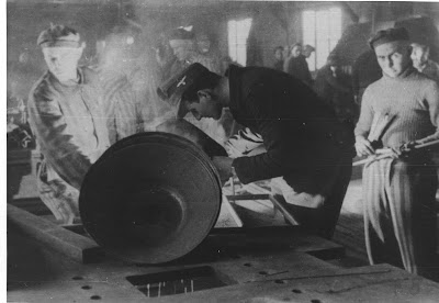 Photo was taken in the camp metal workshop. In the foreground, SS man Edward Lubusz who provided Galiński with the SS uniform before the planned escape, and next to him is Edward Galiński.