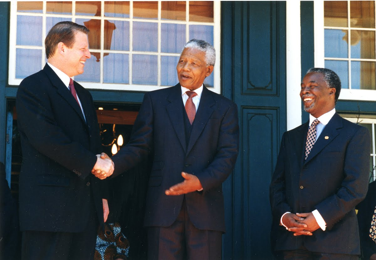 Nelson Mandela jokes outside his Cape Town office, Tuynhuys with US Vice-President Al Gore while South African Deputy President Thabo Mbeki looks on.