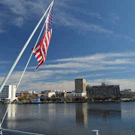 Flag on the River by Thomas Shaw - City,  Street & Park  Skylines ( water, sky, flag, america, blue, wilmington, ship, buildings, cape fear, north carolina, river )