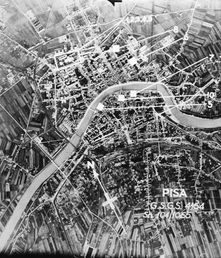 Aerial photograph of Pisa after bombing, showing damage and bomb craters at railroad yards in the foreground and undamaged historic monuments to the north, which had been identified on the map prepared by the Committee.
