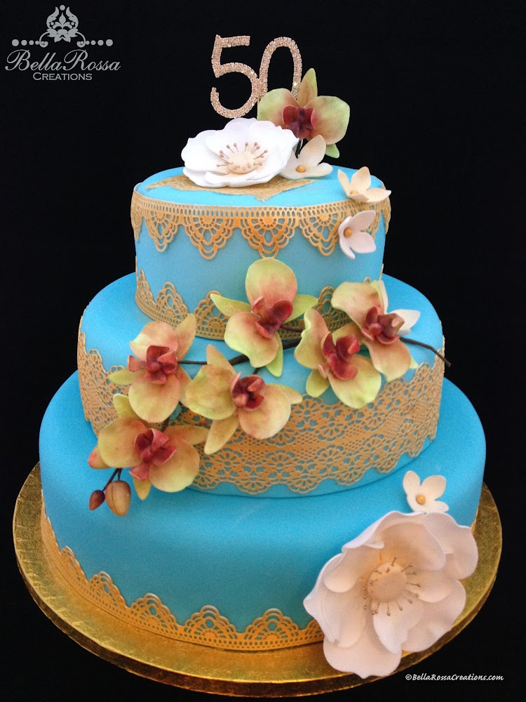 3-tier 50th Wedding Anniversary cake. Each cake tier consisted of different flavours surrounded with golden sugar lace. The middle tier was embellished with a lovely handcrafted bunch of orchids made from gum paste. Finally, the top tier was finished with handcrafted full blooming gum paste flowers. This cake was inspired by the celebrator's dress and the orchid themed table arrangements!.