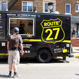 Route 27 by Ronnie Caplan - City,  Street & Park  Neighborhoods ( sign, logo, menus, facade, street fair, tires, buildings, windows, food truck, people, black, man )