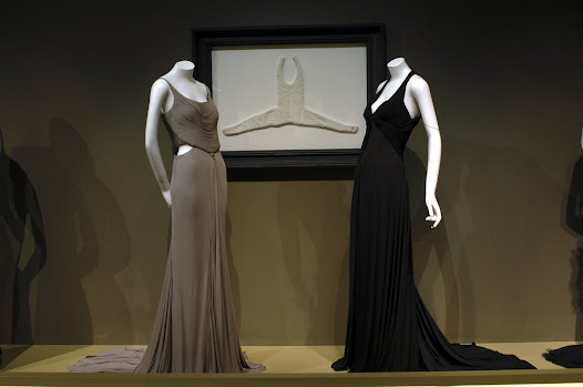 The bodices of the two jersey evening gowns, and the one hanging on the wall, borrow a pleating technique known as fluting, perfected by Madame Grès.
