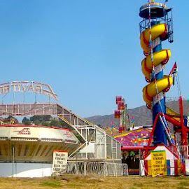 No Amusement Park by Ronnie Caplan - City,  Street & Park  Amusement Parks ( signs, flags, amusement park, delapidated, fence, mountains, rides, tents, sky, colourful, malibu, slide, abandoned )