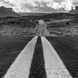 On the Road to Professor Valley by Robert Carney - Landscapes Deserts ( clouds, moab, mountains, desert, highway, utah, black and white, b&w, landscape )