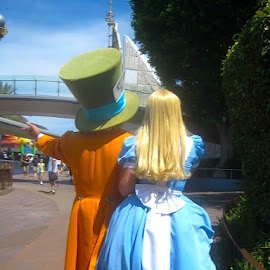 Alice & the Mad Hatter by Ronnie Caplan - People Musicians & Entertainers ( costumes, walking, street, theme park, hat, performers, sky, blue, shadow, dress, trees, disneyland, avenie, characters )