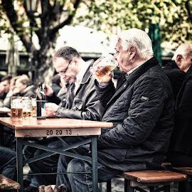 Biergarten by Johannes Oehl - City,  Street & Park  Street Scenes ( old, bench, bottle, spring, munich, sitting, beer, vikualienmarkt, germany, men, dog, springtime, man, outside )