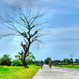 Bikers by Anjun Manzano - Sports & Fitness Cycling ( tree, grass, road, people, bicycle )