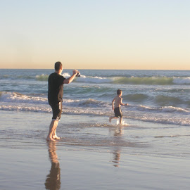 Dad and son playing catch on the beach by Linda McCormick - People Street & Candids ( dad, beach fun, football, catch, son )
