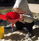 Child pouring dry sand through funnel