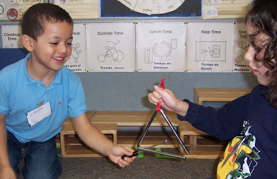 Children feeling the vibration made by a music triangle when struck.