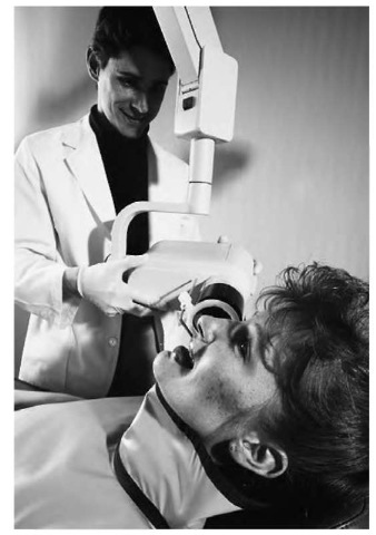 """""""Soft"""" x-ray machines, such as this one being used by a dentist to photograph the patient's teeth, operate at relatively low frequencies and thus don't harm the patient."""