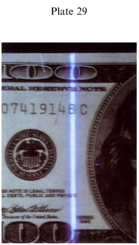Plate 29 FORGERY AND FRAUD/Counterfeit Currency Fluorescence of counterfeit $100 FRN simulated security thread.
