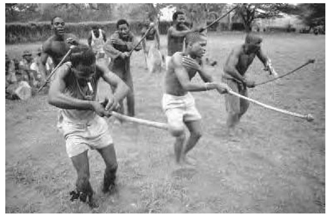 Many African combat systems relied heavily on the rehearsal of combat movements through dances. Here, game preserve guards in Ndumu, South Africa, practice a martial dance using rungu (knobbed sticks) in conjunction with the rhythm from percussion instruments, 1980.