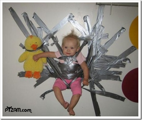 Picture of a baby duct taped to a wall.