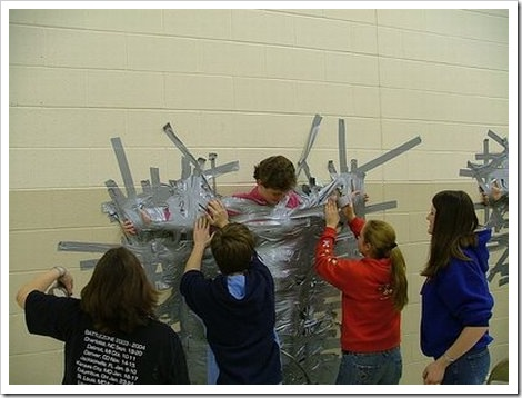 Picture of a woman being duct taped to a wall.
