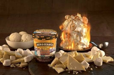 Tub of ben & Jerry's Ice cream on a table, surrounded by chocolate pieces, ice cream and a flaming baked alaska