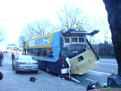 Photo shows roof of bus from rear on the road. Back window is totally smashed as is the surrounding metal. A fire engine can be seen in the background. Photo taken at 08:12