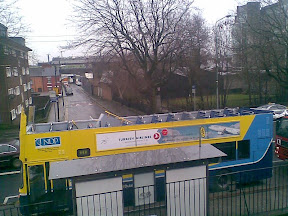 photo shows Dublin Bus parked beside railings with Fire engine parked behind. The top of the bus is completely gone, you can actually count all the seats upstairs.