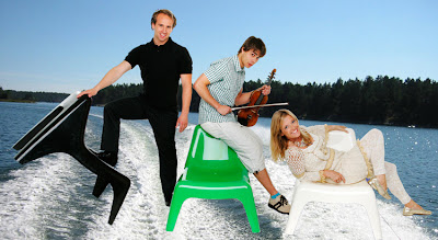 image shows three people with a lake and waterski-trails photoshopped into the background, while they're sitting on brightly neon coloured plastic chairs.