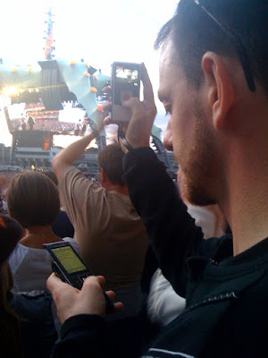 Holding a flip camera in one hand recording the U2 concert in Croke Park and tweeting from a mobile phone in the other