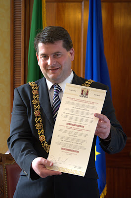 Cork's Lord Mayor Dara Murphy holding a decree scroll