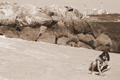 Menina brinca na areia da praia de Albarquel