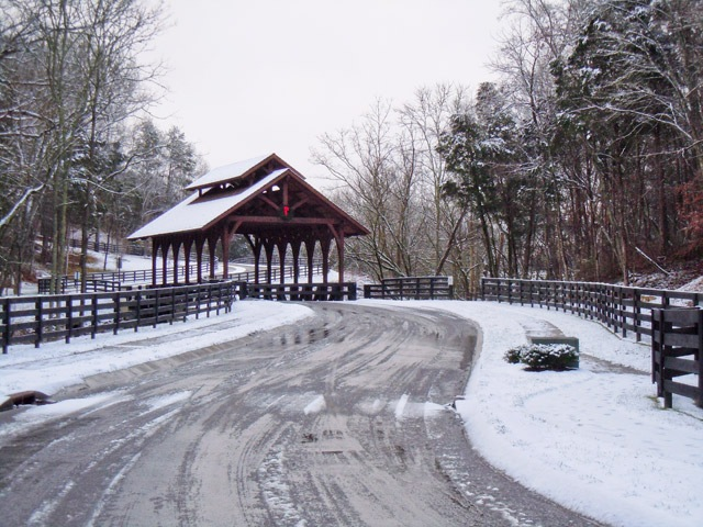 covered bridge entrance with snowfall