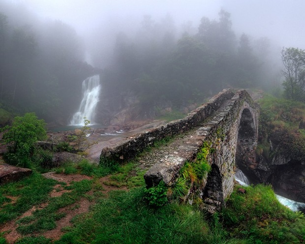 The stone bridge of Tallorno under a thick fog and some light rain in Val Chiusella, Piedmont, Italy