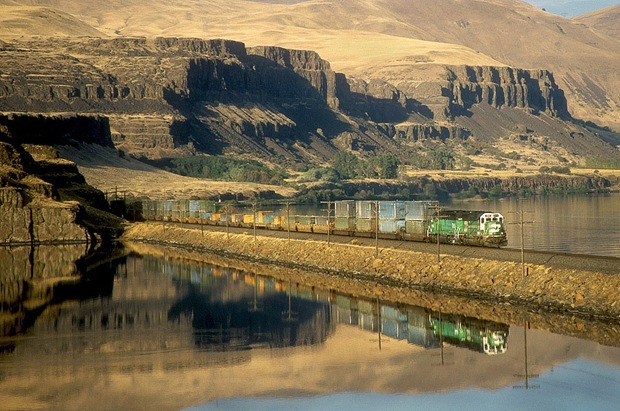 The last light of day sees an empty garbage train heading West along the Columbia River in North Dalles, Washington.
