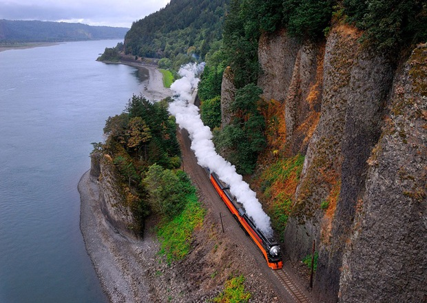 A steam train runs alongside the river and rock at Washougal, Washington, USA
