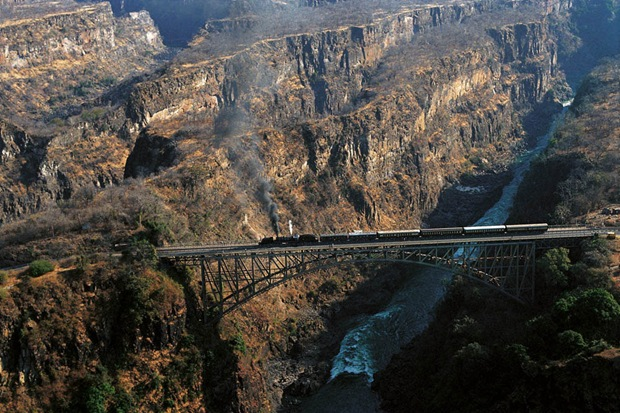 Train runs over a bridge through an amazing landscape at ZimbabweVictoria Falls