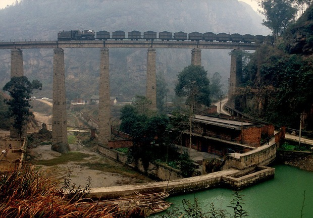 Train passes through and old bridge in Weiyuan, China