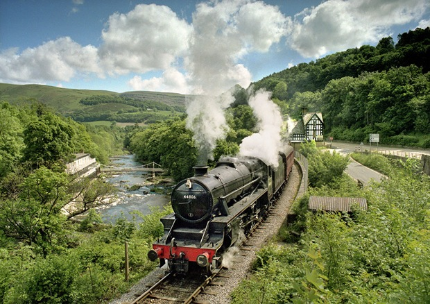A steam locomotive runs through the green landscape at Berwyn at Denbighshire in Wales, UK
