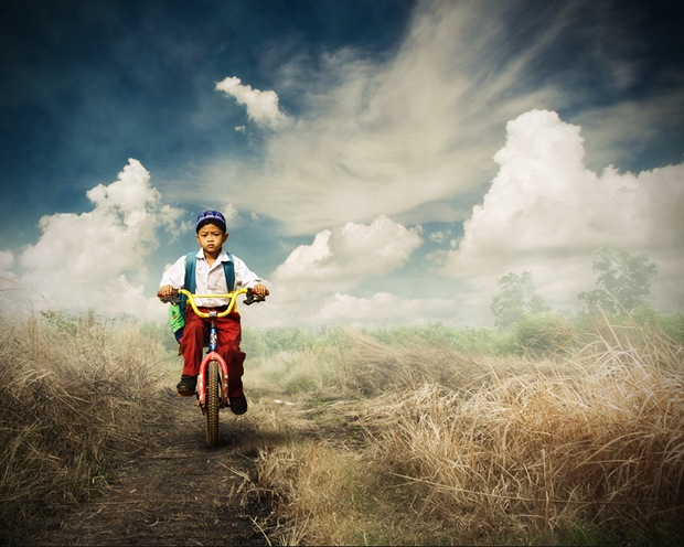 An Indonesian elementary student goes to school with a bike through a barren land.