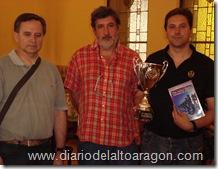 el MF. Javier Fontana con su trofeo de vencedor y material de ajedrez posando con Juan Carlos González (centro) y Roberto Cifuentes (izquierda).